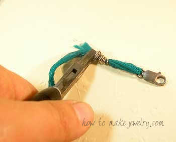 Use your flat nose or chain nose pliers to squeeze the end down and tuck it in.