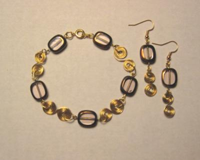 A combination of smoky colored stones and golden swirls with matching earrings.