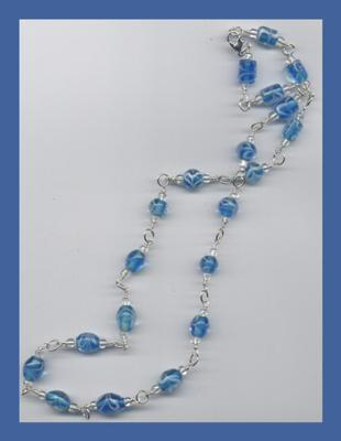 Wire wrapped blue glass beads on a silver chain make for a beautiful necklace by Laurie~!