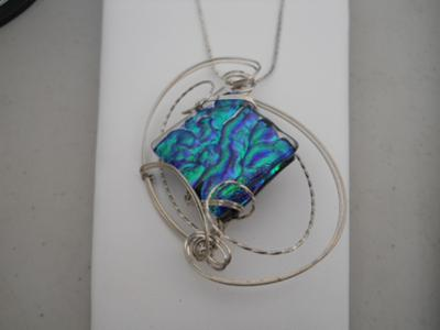 Argentium (non-tarnish) sterling silver wire sculpted dichroic piece of glass.